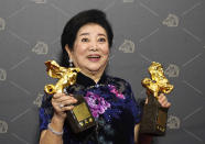 "Taiwanese actress Chen Shu-fang holds her awards for Best Leading Actress and Best Supporting Actress at the 57th Golden Horse Awards in Taipei, Taiwan, Saturday, Nov. 21, 2020. Chen won for the film ""Dear Tenant"" at this year's Golden Horse Awards - one of the Chinese-language film industry's biggest annual events. (AP Photo/Billy Dai)"