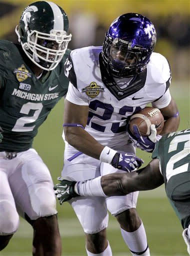 TCU running back B.J. Catalon (23) gains yards as Michigan State Spartans defensive end William Gholston (2) defends during the first half of the Buffalo Wild Wings Bowl NCAA college football game, Saturday, Dec. 29, 2012, in Tempe, Ariz. (AP Photo/Matt York)