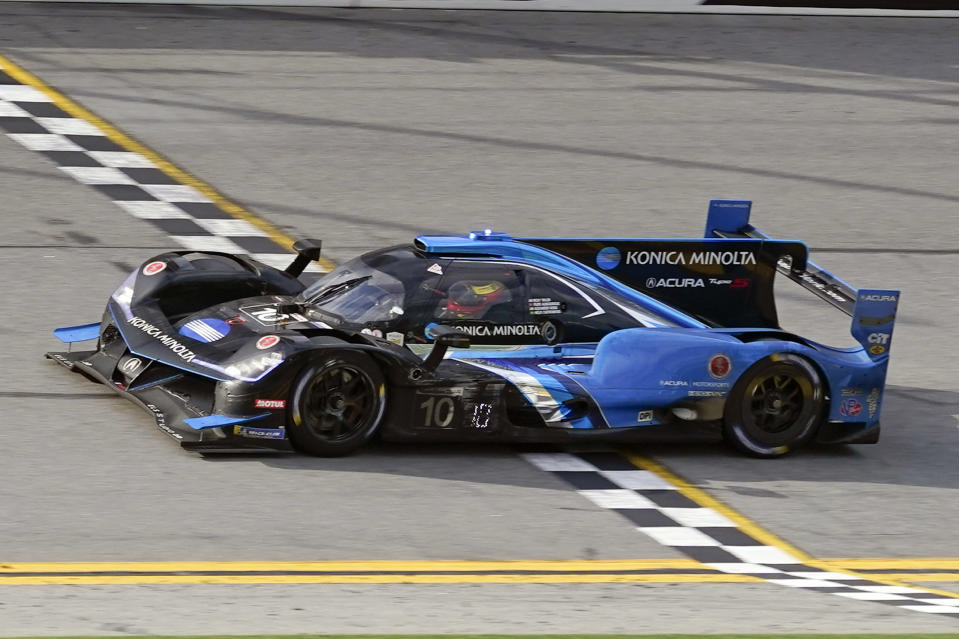 Filipe Albuquerque crosses the finish line in his Acura DPi to win the Rolex 24 hour auto race at Daytona International Speedway, Sunday, Jan. 31, 2021, in Daytona Beach, Fla. (AP Photo/John Raoux)