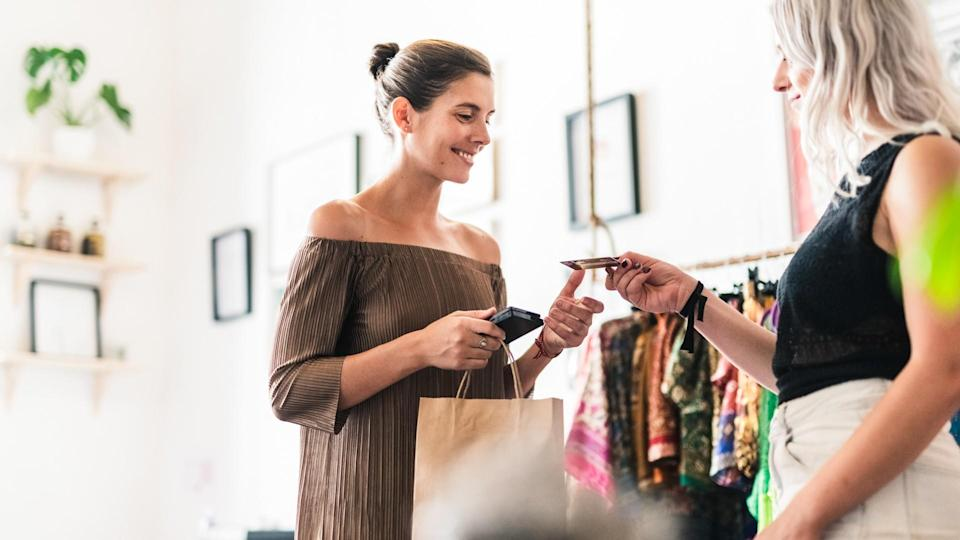 Smiling woman doing credit card purchase.