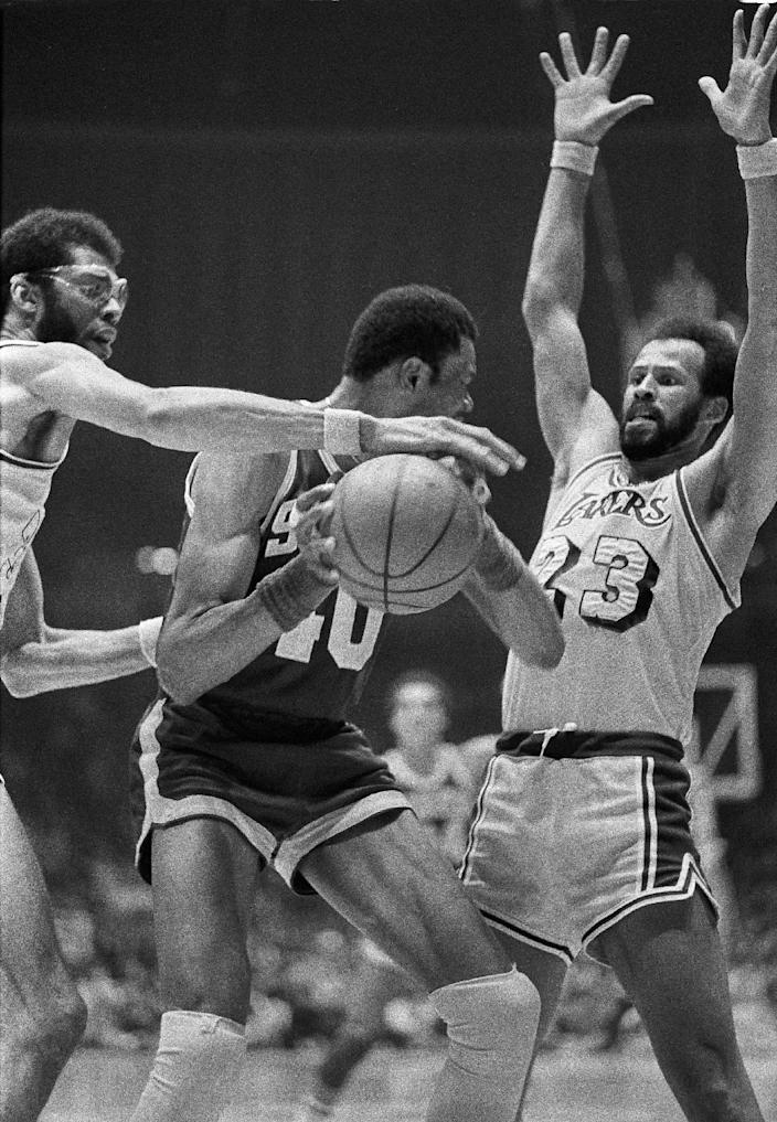FILE - In this April 15, 1978 file photo, Los Angeles Lakers' Kareem Abdul-Jabbar, left, reaches for the ball held by Seattle Supersonics Marvin Webster, center, as Lakers' Lou Hudson (23), right, defends during an NBA playoff game in Los Angeles. Six-time All-Star Lou Hudson died Friday, April 11, 2014, in Atlanta, the Atlanta Hawks said. He was 69. (AP Photo/File)