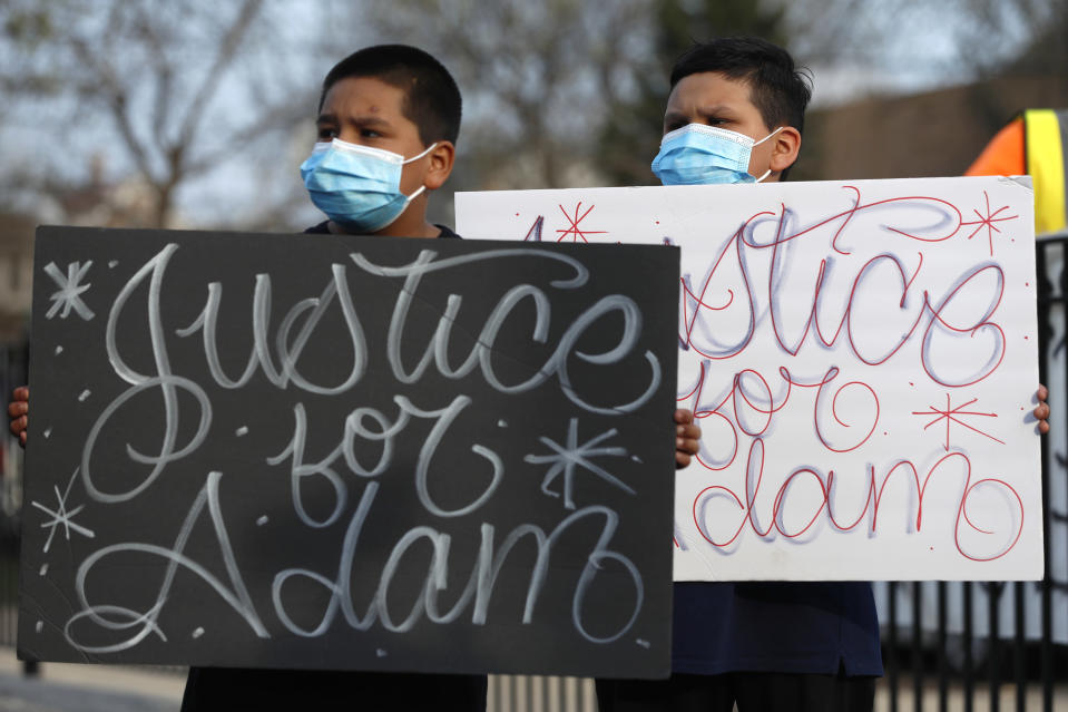 Jacob Perea, 7, left and Juan Perea, 9 holds signs on Tuesday, April 6, 2021, as they attend a press conference following the death of 13-year-old Adam Toledo, who was shot by a Chicago Police officer at about 2 a.m. on March 29 in an alley west of the 2300 block of South Sawyer Avenue near Farragut Career Academy High School. (AP Photo/Shafkat Anowar)