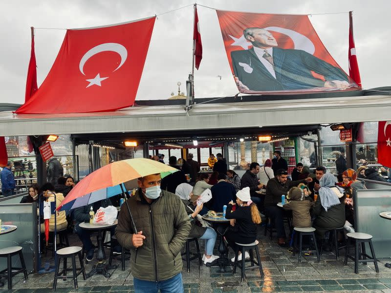 FILE PHOTO: Man wearing a protective mask stands in front of a fish and bread restaurant in Istanbul