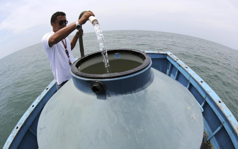 A man on a boat collects water from the ocean to be converted to drinking water through the process of desalination, in Bertioga February 24, 2015.  REUTERS/Paulo Whitaker (BRAZIL - Tags: ENVIRONMENT SCIENCE TECHNOLOGY)