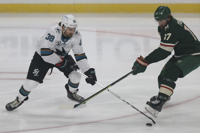 Minnesota Wild's Marcus Foligno (17) and San Jose's Mario Ferraro (38) go after the puck in the first period of an NHL hockey game Sunday, Jan. 24, 2021, in St. Paul, Minn. (AP Photo/Stacy Bengs)