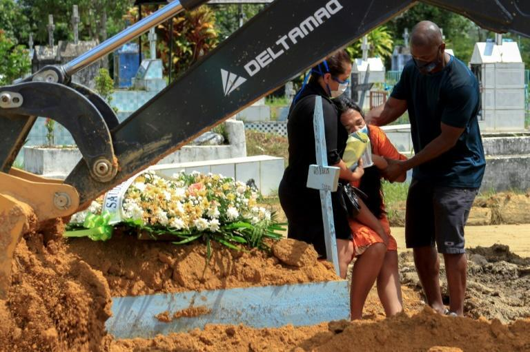In this file photo taken on January 22, 2021 relatives of a Covid-19 victim mourn during a funeral at the Nossa Senhora Aparecida cemetery in Manaus, Brazil