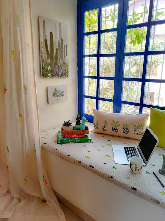 This blue-framed bay window packs in a wide seating area that serves as Kajal's home office with a view.