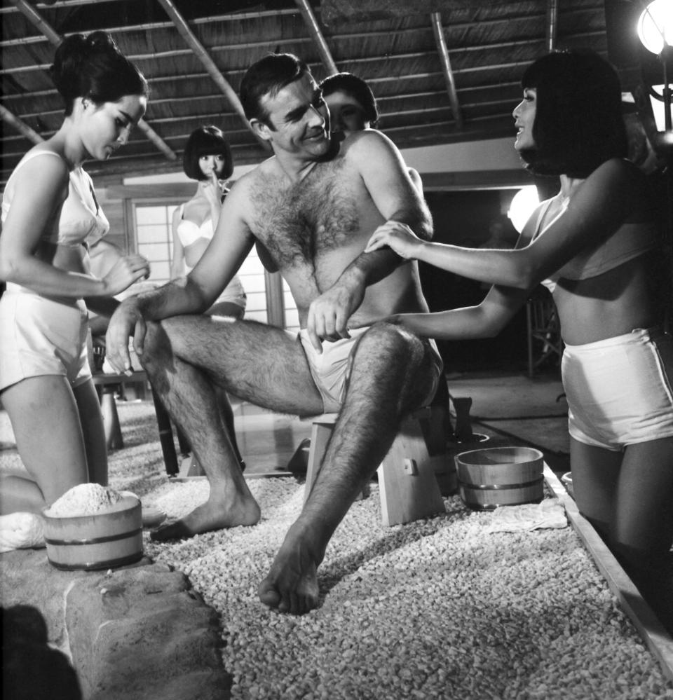 FILE - In this file photo dated Sept. 26, 1966, British actor Sean Connery, being given a Japanese bath, during filming of a scene in the James Bond film, You Only Live Twice, at Pinewood Studios near London. The actresses shown are Yasuko Nagazuni, at left and Yee Wah Yang at right. Scottish actor Sean Connery, considered by many to have been the best James Bond, has died aged 90, according to an announcement from his family. (AP Photo/Sidney Smart, FILE)