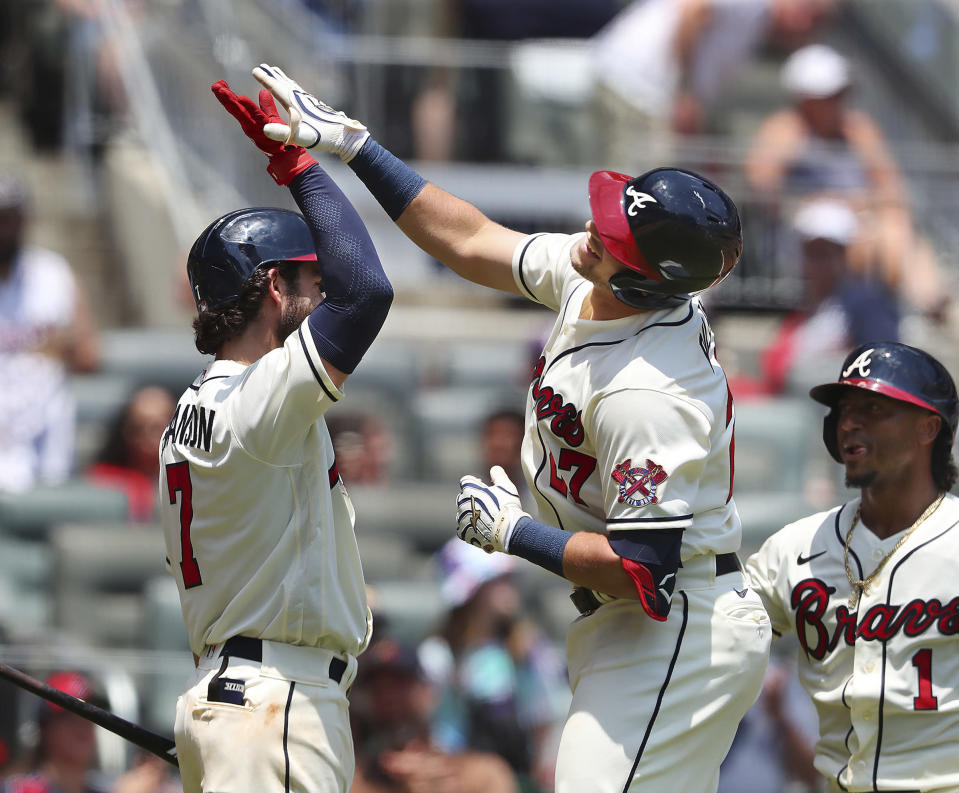 Atlanta Braves' Austin Riley, center, gets some air to high-five teammate Dansby Swanson, left, while celebrating his second home run with Ozzie Albies, right, looking on during the third inning of a baseball game against the Pittsburgh Pirates, Sunday, May 23, 2021, in Atlanta. (Curtis Compton/Atlanta Journal-Constitution via AP)