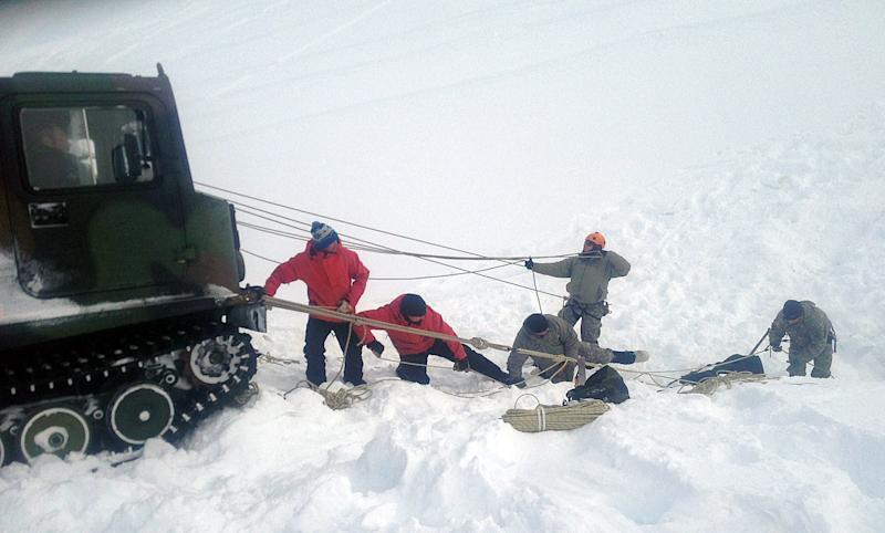 In this photo provided by the U.S. Army and taken Sunday April 14, 2013, members of the Army's Alaska Northern Warfare Training Center prepare to descend 145 feet to a 15-foot space inside an Alaskan glacier in the Hoodoo Mountains to extract the body of a 9-year-old boy who fell through the hole on his snowmobile on Saturday. The men on Sunday shoveled 3,000 pounds of snow into bags lifted out by soldiers at the surface to reach the body of Shjon Brown. (AP Photo/U.S. Army)