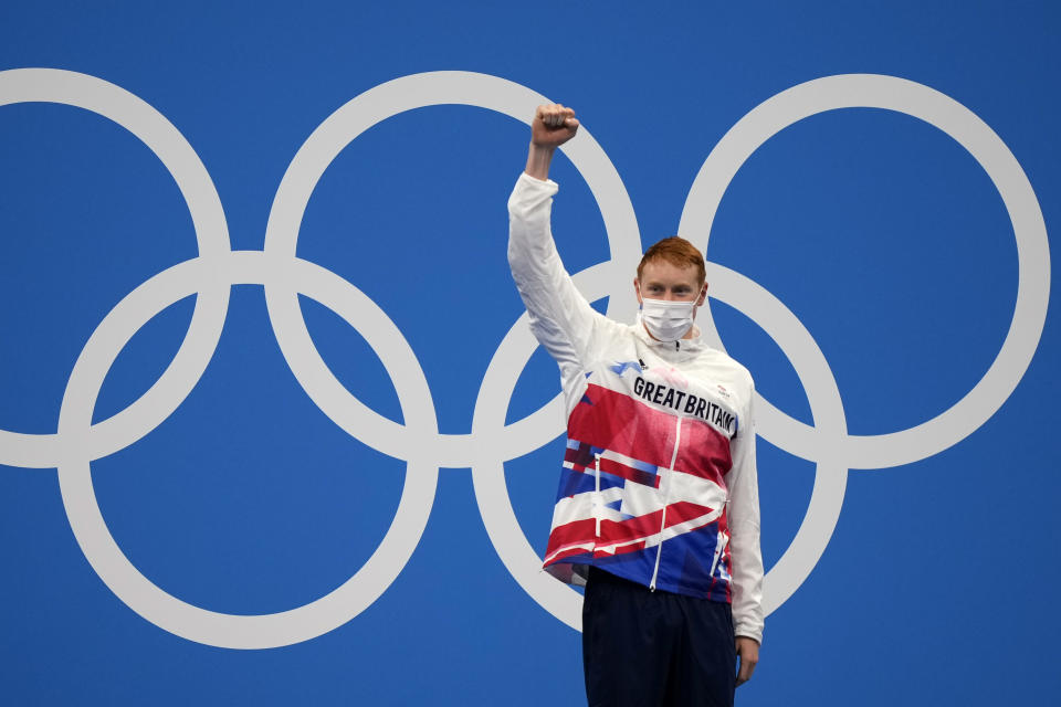 Tom Dean of Britain celebrates on the podium after winning the final of the men's 200-meter freestyle at the 2020 Summer Olympics, Tuesday, July 27, 2021, in Tokyo, Japan. (AP Photo/Martin Meissner)