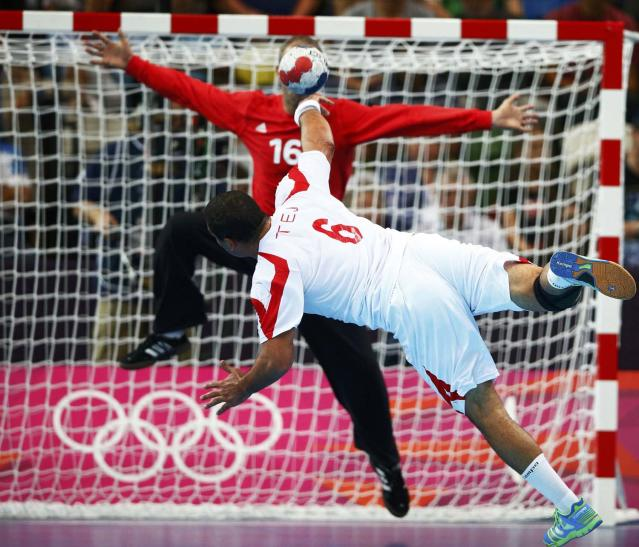 Tunisia's Issam Tej scores on France's goalkeeper Thierry Omeyer in their men's handball Preliminaries Group A match at the Copper Box venue during the London 2012 Olympic Games August 2, 2012. REUTERS/Marko Djurica (BRITAIN - Tags: SPORT TPX IMAGES OF THE DAY SPORT HANDBALL OLYMPICS)