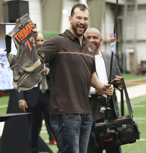 Cleveland Browns' offensive lineman Joe Thomas accepts his parting gift of fishing gear from head coach Hue Jackson as Thomas bids farewell and thanks to the owners, coaches, staff and fans during a news conference, Monday, March 19, 2018, at the Browns' headquarters in Berea, Ohio. Thomas is retiring after 11 NFL football seasons. The 10-time Pro Bowler announced his retirement, ending a career marked by durability and dominance. (John Kuntz/The Plain Dealer via AP)