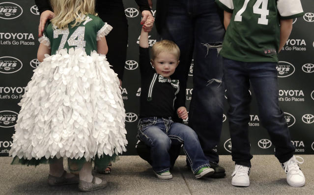 Thomas Mangold, center, son of New York Jets center Nick Mangold, rests on his father's foot during a family portrait at a news conference making Nick Mangold's official retirement from NFL football, Tuesday, April 24, 2018, in Florham Park, N.J. Mangold announced his retirement a week earlier in a post on Twitter. He was selected to seven Pro Bowls and was twice a first-team All-Pro during his 11-year career. (AP Photo/Julio Cortez)