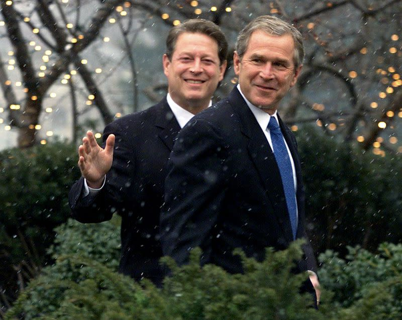 FILE PHOTO: Vice President Al Gore (L) waves as he escorts President-elect George W. Bush into his residence aft..