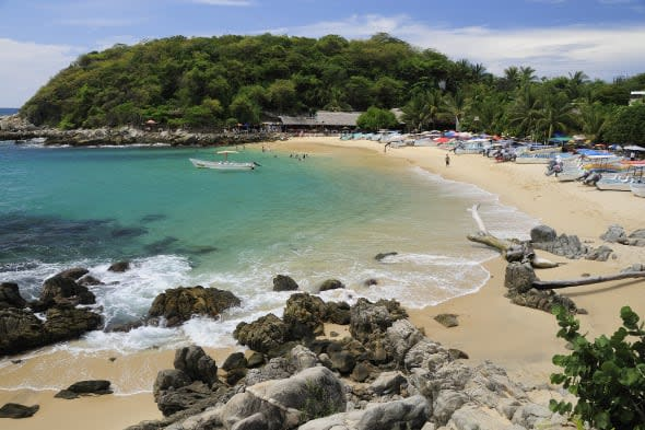 Mexico, Oaxaca, Puerto Escondido, View onto Playa Manzanillo beach with rocks and driftwood in foreground, tourist boats, people