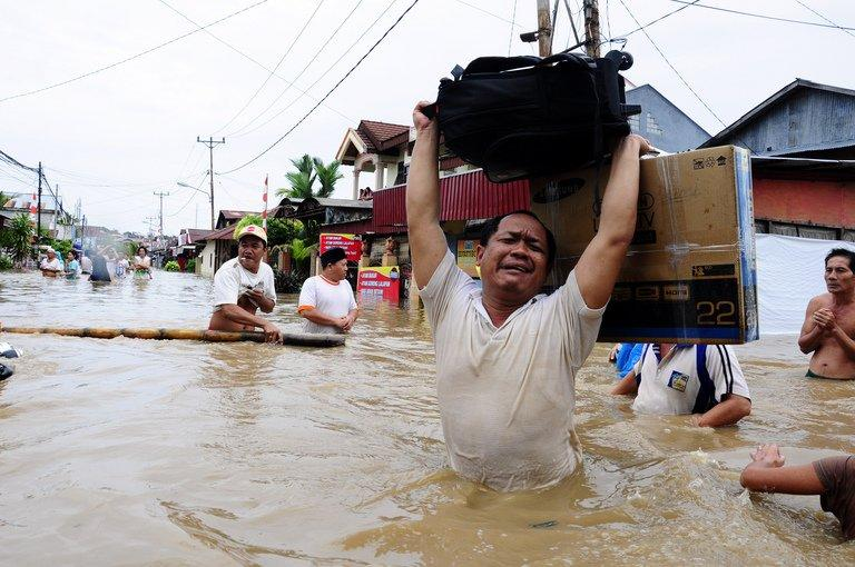 Residents salvage their belongings while floods inundate the city of Manado on February 17, 2013