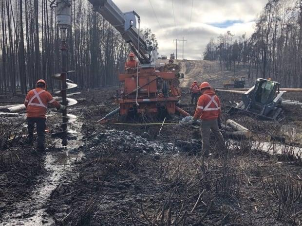 SaskPower equipment got stuck in the mud throughout Thursday, as workers tried to fix fire-damaged power structures.