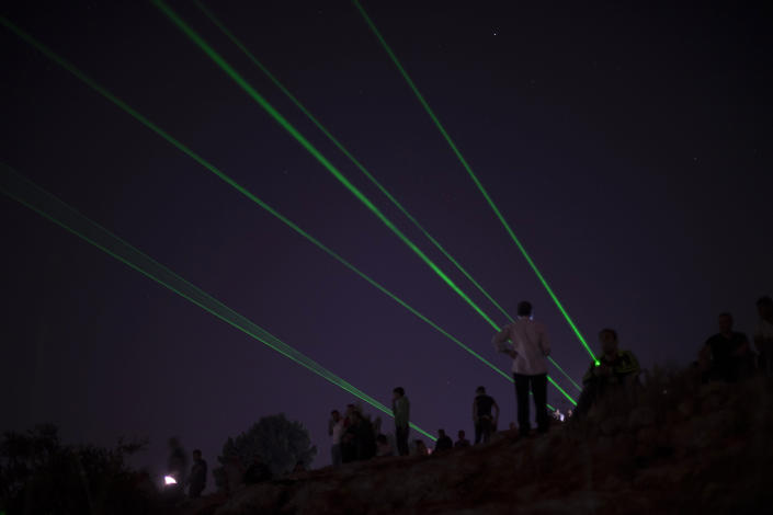 Palestinian demonstrators shine laser torches during a demonstration against the West Bank Jewish settlement outpost of Eviatar that was rapidly established last month, at the Palestinian village of Beita, near the West Bank city of Nablus, Sunday, June 27, 2021. The Palestinians say it was established on their farmland and fear it will grow and merge with other large settlements in the area. (AP Photo/Majdi Mohammed)