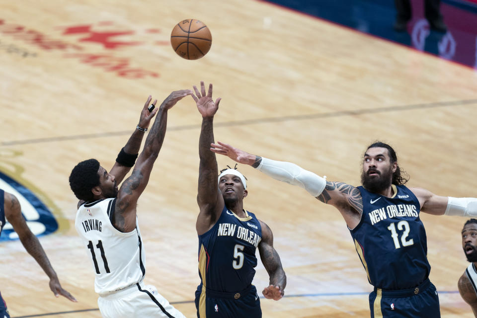 Brooklyn Nets guard Kyrie Irving (11) shoots against New Orleans Pelicans guard Eric Bledsoe (5) and center Steven Adams (12) in the first half of an NBA basketball game in New Orleans, Tuesday, April 20, 2021. (AP Photo/Gerald Herbert)