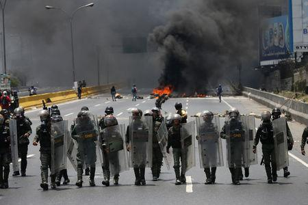 Riot police take position as demonstrators rally against Venezuela's President Nicolas Maduro's government in Caracas