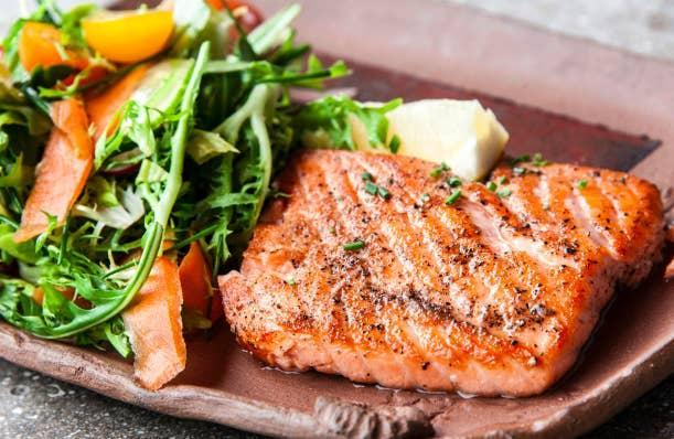 A plate of cooked salmon with a side salad