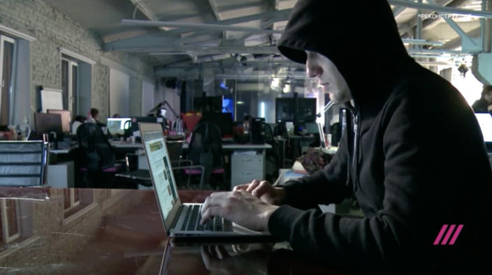 """Screen grab of """"Maksim"""" with his face concealed, a former member of the Internet Research Agency troll factory's elite English language department. (Video still: TV Rain)"""