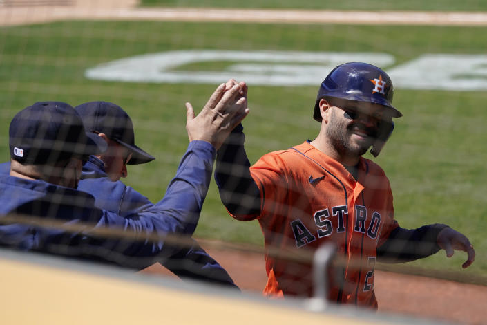 Houston Astros' Jose Altuve, right, is congratulated after scoring against the Oakland Athletics during the seventh inning of a baseball game in Oakland, Calif., Thursday, May 20, 2021. (AP Photo/Jeff Chiu)