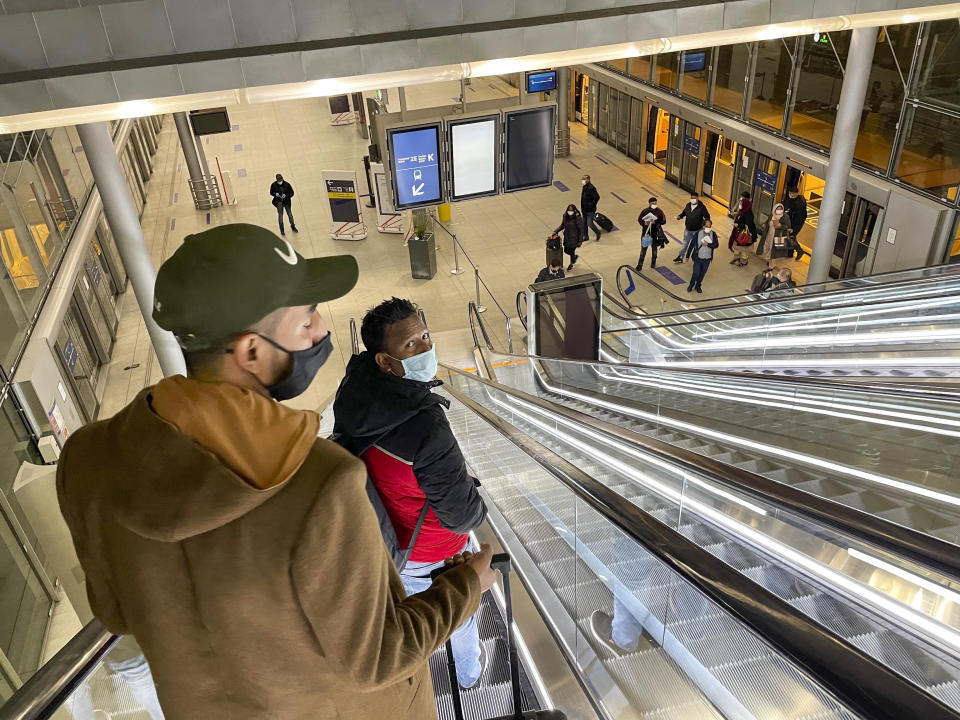 Arriving and departing passengers use the train link between two terminals at Paris Charles de Gaulle airport Tuesday Dec. 22, 2020. More and more countries around the world are restricting travel from Britain and elsewhere, including South Africa, amid concerns about new strains of the coronavirus, forcing many passengers to reroute their trips. (AP Photo/Jerome Delay)
