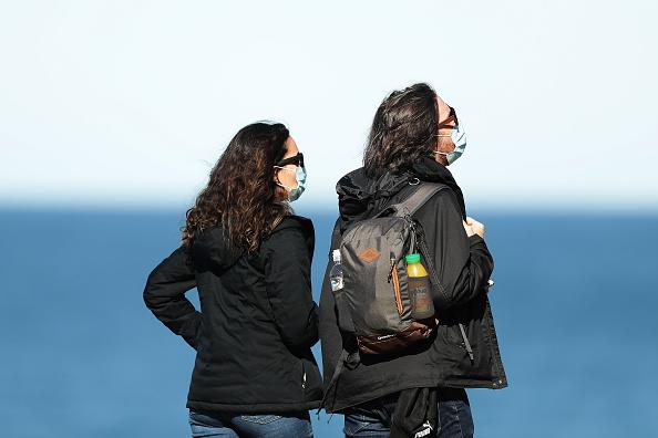A couple wear face masks while walking at Bondi Beach  in Sydney, Australia.