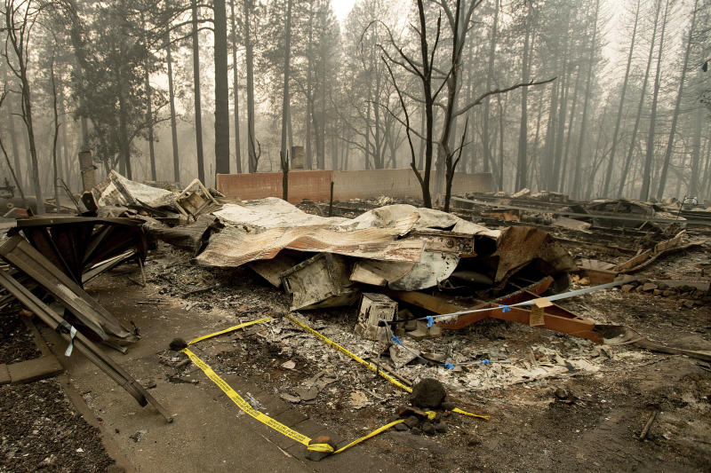 """FILE - In this Wednesday, Nov. 14, 2018 file photo, tape marks a spot where sheriff's deputies recovered the body of a Camp Fire victim in Paradise, Calif. The body count from California's deadliest wildfire is back down to 85 after authorities determined that a bone fragment previously classified as """"unidentified"""" belongs to a victim named back in January. The Butte County Sheriff's office said Wednesday, Sept. 25 2019 that the number of unidentified victims from the November 2018 Camp Fire now stands at one (AP Photo/Noah Berger, File)"""