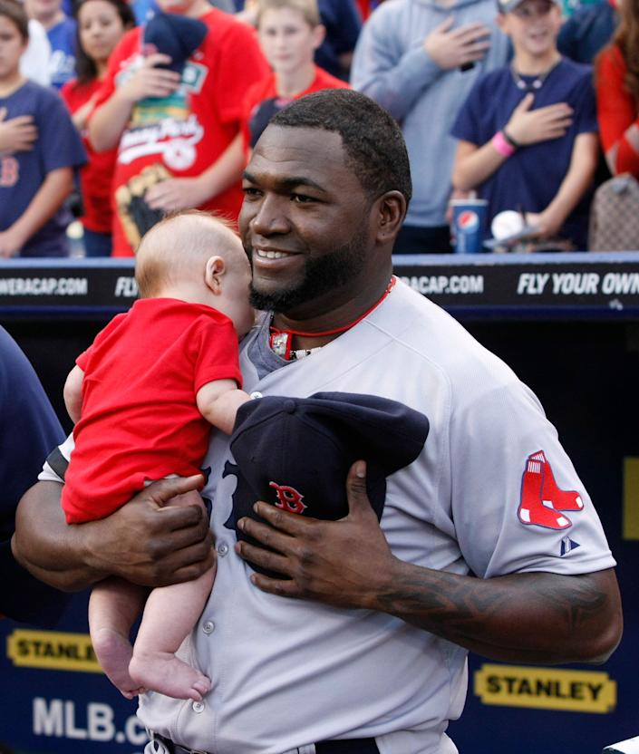 Boston Red Sox' David Ortiz holds a fan's baby during the national anthem before their baseball game against the Kansas City Royals at Kauffman Stadium in Kansas City, Mo., Thursday, Aug. 8, 2013. (AP Photo/Colin E. Braley)