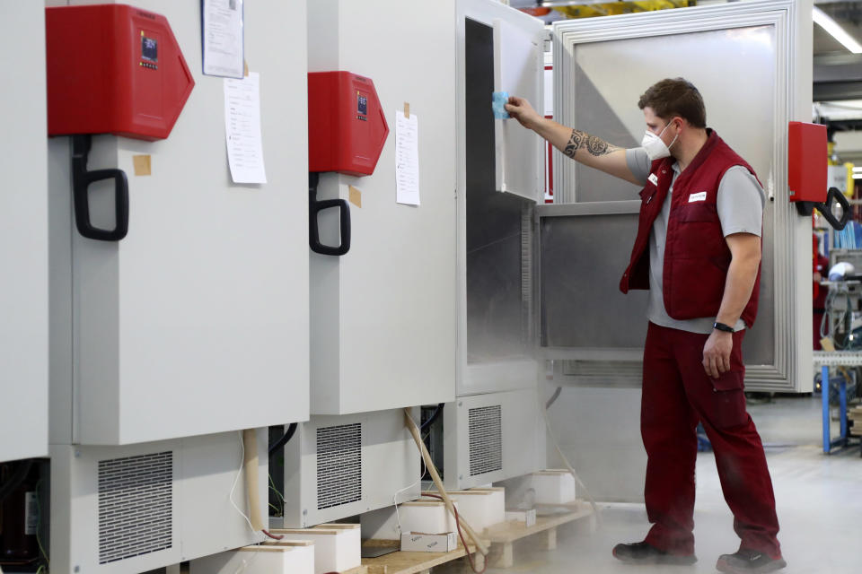 File -- In this Tuesday, Nov. 24, 2020 file photo an employee of Binder, the world's largest manufacturer of serial-production environmental simulation chambers for scientific or industrial laboratories, checks an ultra low temperature freezer in Tuttlingen, Germany. Germany prepares for the vaccination of the German population during the upcoming month. (AP Photo/Matthias Schrader, file)
