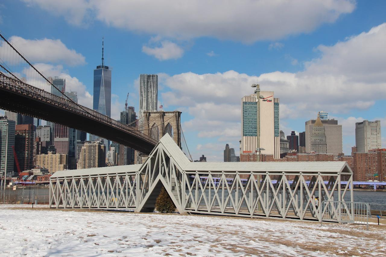 Located in New York's Brooklyn Bridge Park is <em>Bridge Over Tree</em>, a sculptural installation designed by Iranian-born, Minneapolis-based artist Siah Armajani. The work was first shown as a temporary sculpture in Minneapolis in 1970, and is now on view for the public for the first time in nearly 50 years. It comprises a 91-foot-long bridge and a set of stairs at the sculpture's midpoint. These stairs send visitors up and down over a small evergreen tree. The sculpture was designed to force complete strangers to pass, interact, and cooperate with one another when passing the center of the structure. In a moment of heated political disagreement, finding common ground with any stranger is a welcome change.