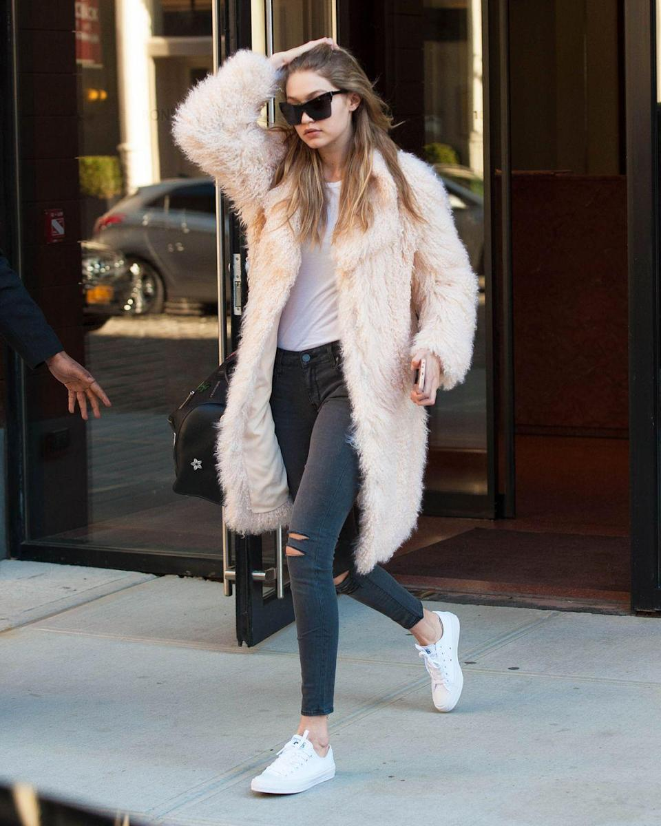 <p>Out in New York City wearing a pale pink faux-fur coat with a white tee and distressed Parker Smith jeans, plus Converse sneakers and Elizabeth and James sunglasses. </p>