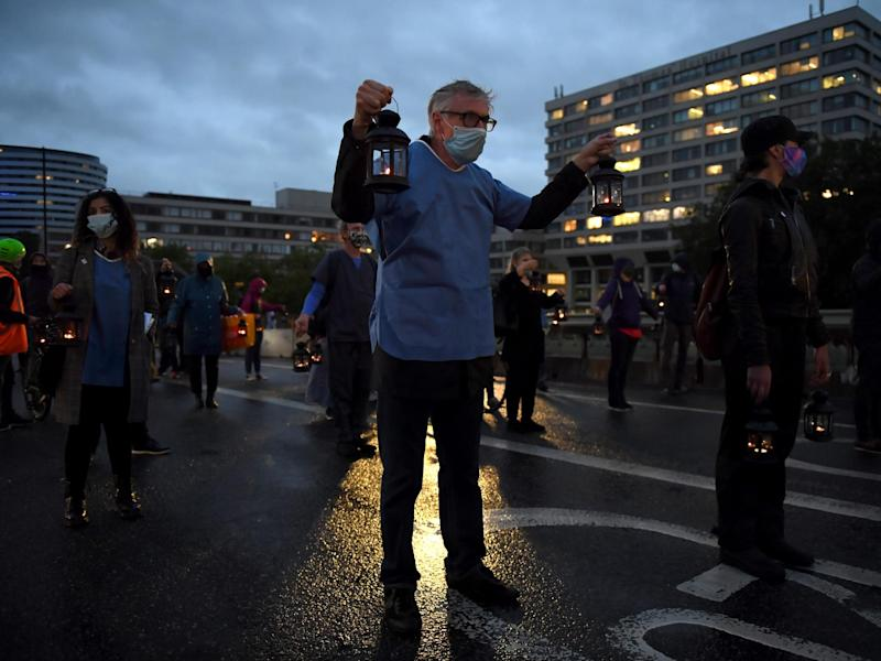 People wearing face masks and holding lanterns attend a vigil for the victims of the coronavirus on Westminster Bridge on 3 July 2020 in London, England: Photo by Chris J Ratcliffe/Getty Images