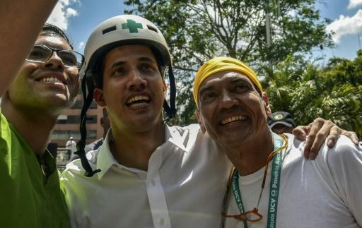 Venezuelan opposition leader and self-declared acting president Juan Guaido wears a Green Cross helmet as he posses for a picture with volunteers ready to help bring aid into the stricken country