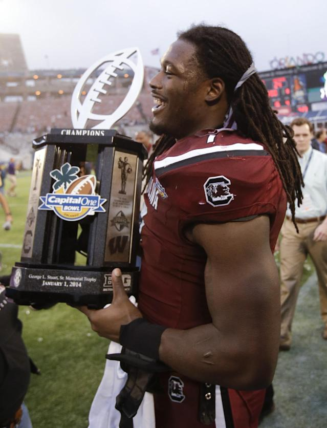 South Carolina defensive end Jadeveon Clowney walks around the field carrying the trophy after South Carolina defeated Wisconsin 34-24 the Capital One Bowl NCAA college football game in Orlando, Fla., Wednesday, Jan. 1, 2014. (AP Photo/John Raoux)