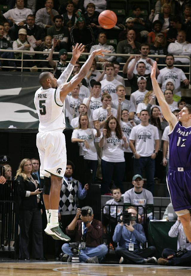 Michigan State's Adreian Payne (5) shoots a three-pointer against Portland Thomas Van Der Mars (12) during the first half of an NCAA college basketball game, Monday, Nov. 18, 2013, in East Lansing, Mich. (AP Photo/Al Goldis)