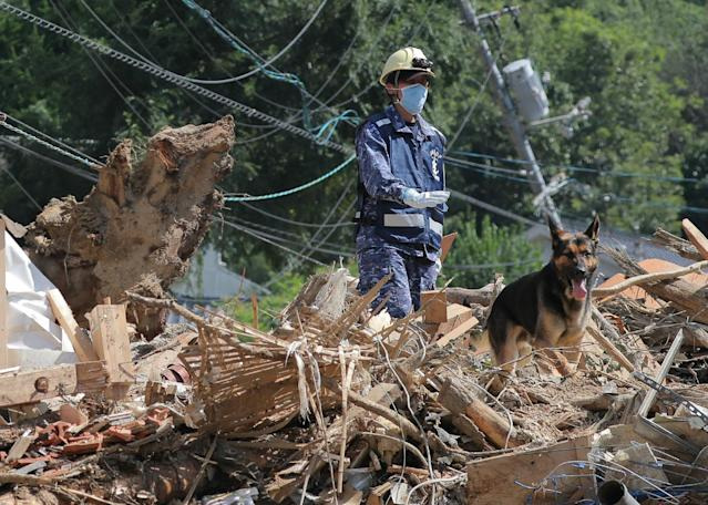 <p>A member of Maritime Self Defense Forces searches for missing persons at a flood damage site in Kure, Hiroshima prefecture on July 12, 2018. (Photo: JiJi Press/AFP/Getty Images) </p>