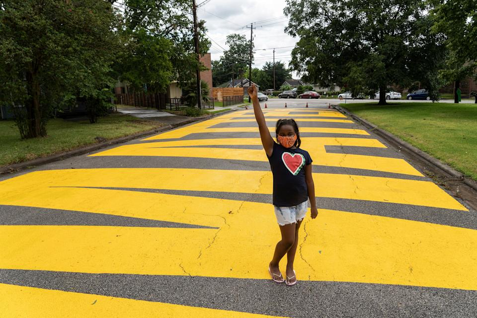 Kainaan Jones, 9, poses on 'Black Towns Matter' painted on a street on 19 June, 2020 in Houston, Texas. (Getty Images)