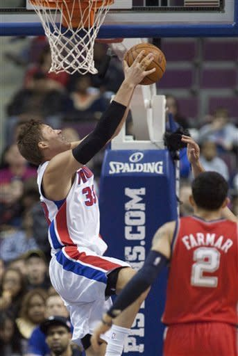 Detroit Pistons' Jonas Jerebko, left, takes a shot under the basket as New Jersey Nets' Jordan Farmar looks on in the first half of an NBA basketball game Friday, Feb. 10, 2012, in Auburn Hills, Mich. (AP Photo/Duane Burleson)