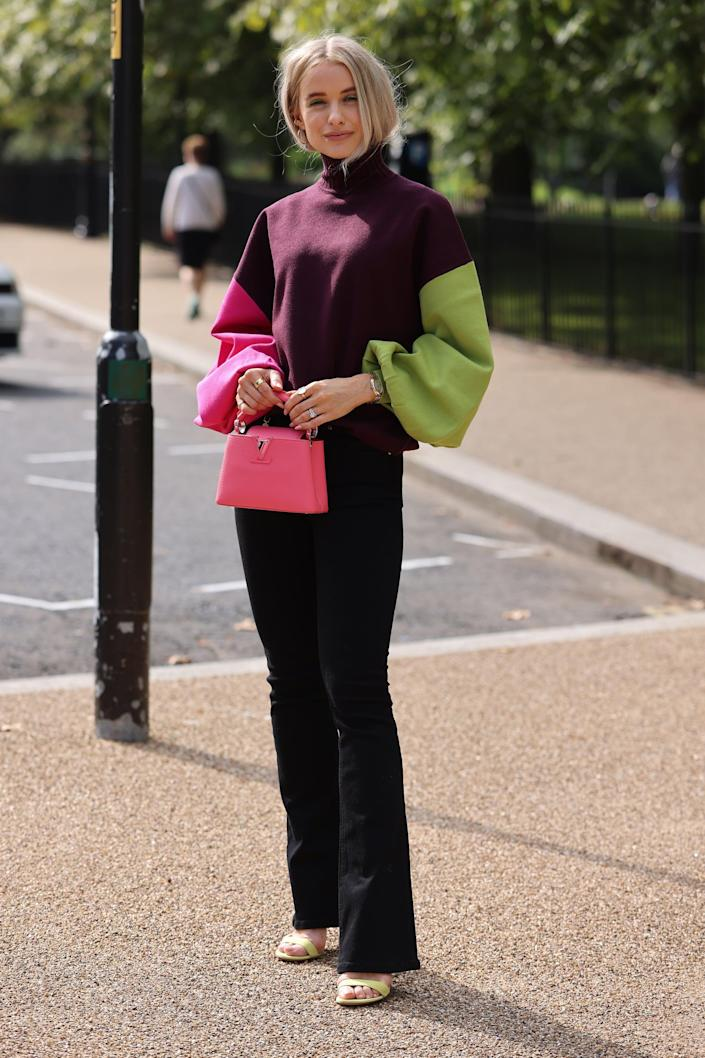 <p>Giving black trousers a little more life is easy with a colorblocked knit and a pop of pink on your bag. </p>