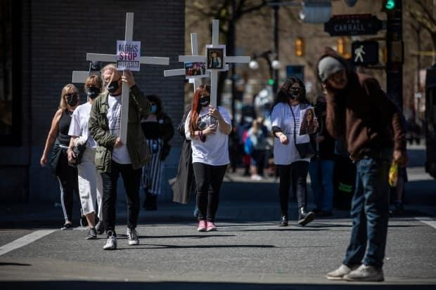Members of Moms Stop the Harm walk down Hastings Street in Vancouver to mark the five-year anniversary of B.C.'s overdose crisis in April 2021.  (Ben Nelms/CBC - image credit)