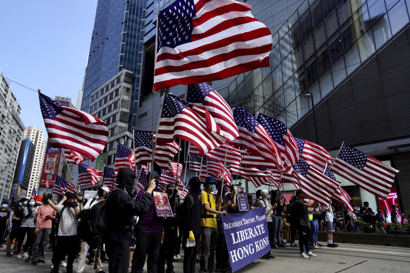 Protesters carry U.S. flags during a rally in Hong Kong, Sunday, Sept. 15, 2019. Thousands of Hong Kong people chanted slogans and marched Sunday at a downtown shopping district in defiance of a police ban, with shops shuttered amid fears of renewed violence in the months-long protests for democratic reforms in the semi-autonomous Chinese territory. (AP Photo/Vincent Yu)