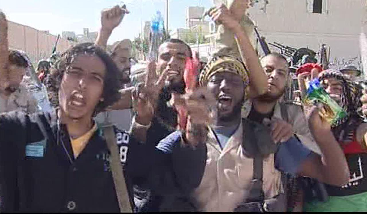 Libyan fighters celebrate in the streets of Sirte Libya in this image taken from TV Thursday Oct. 20, 2011. The Libyan fighters on Thursday overran the remaining positions of Moammar Gadhafi loyalists in his hometown of Sirte, ending the last major resistance by former regime supporters still holding out two months after the fall of the capital Tripoli. Libyan officials and NATO say they cannot confirm reports from revolutionary fighters that ousted Libyan leader Moammar Gadhafi was captured or killed in the fall of his hometown Thursday. (AP Photo/APTN) TV OUT