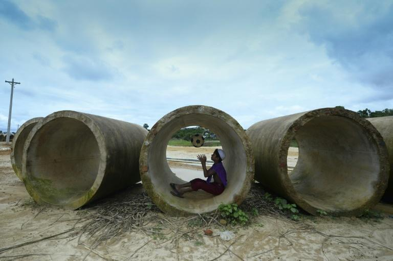 A Rohingya child plays with a football inside a sewage pipe at a refugee camp