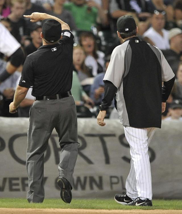 Chicago White Sox manager Robin Ventura, right, looks on while third base umpire Greg Gibson, left, ejects him after Texas Rangers' Ian Kinsler hit an inside-the-park home run during the third inning of a baseball game in Chicago, Friday, Aug. 23, 2013. (AP Photo/ Paul Beaty)