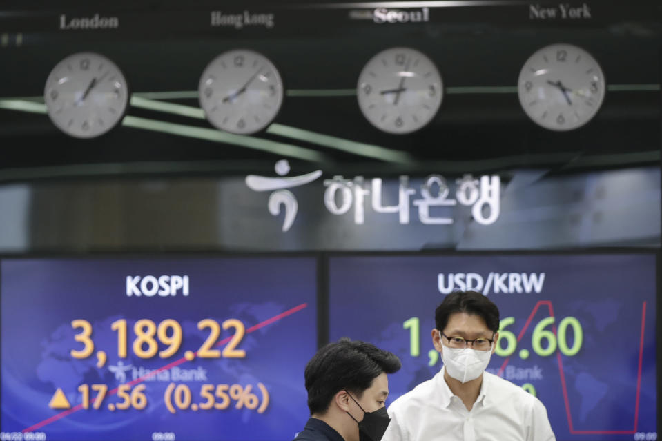 Currency traders talk near screens showing the Korea Composite Stock Price Index (KOSPI), left, and the foreign exchange rate between U.S. dollar and South Korean won at the foreign exchange dealing room of the KEB Hana Bank headquarters in Seoul, South Korea, Thursday, April 22, 2021. Asian shares were higher on Thursday after a broad advance on Wall Street led by technology companies and banks. (AP Photo/Lee Jin-man)