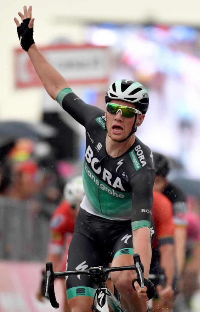 Sam Bennett of Ireland, center, celebrates as he crosses the finish line to win the 12th stage of the Giro dItalia cycling race from Osimo to Imola, Italy, Thursday, May 17, 2018. Bennett opened up his sprint a long way out to storm past Matej Mohoric and Carlos Betancur and claim his second victory of this Giro, as Britain's Simon Yates remained in the overall lead on Thursday. (Daniel Dal Zennaro/ANSA via AP)